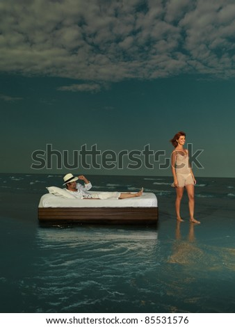 young happy couple on exotic holliday. the man is laying on a bed and the woman is standing, they are surrounded by water.