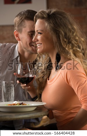 Young happy couple on romantic date drinking glass of red wine at restaurant, celebrating valentine day - stock photo