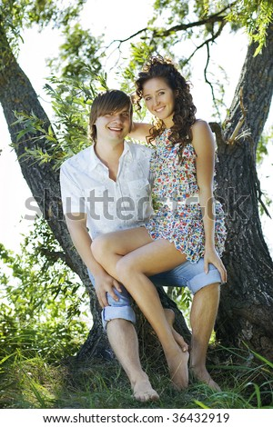 Young happy couple on the island under the tree. - stock photo