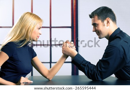 Young happy couple or two businesspeople fighting in arm wrestling, at office - stock photo