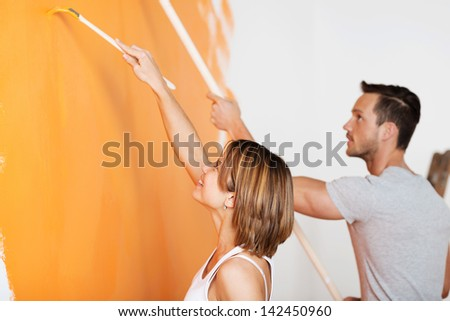 Young happy couple painting wall at new home in orange - stock photo
