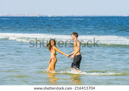 Young happy couple playing on water in the beach. Girl wearing a red, yellow patterned two piece bikini bathing suit, guy wearing a black bathing suit, holding hands each other, smiling.