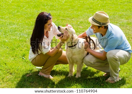 Young happy couple playing with Labrador dog smiling in park - stock photo