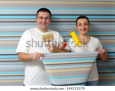 Young happy couple posing against papered wall holding some basic wallpapering tools - stock photo