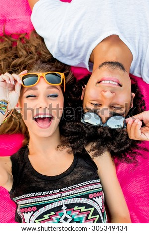 Young happy couple  posing in hot sunny summer day on the beach. Couple in love having fun and enjoying time together.   Friends making grimace  and laughing . Wearing sunglasses. - stock photo