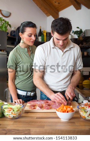 Young happy couple preparing lunch in kitchen
