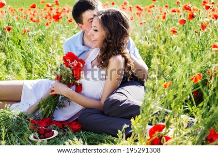 Young happy couple reasting on a meadow full of poppies