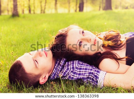 Young happy couple resting on the grass. - stock photo