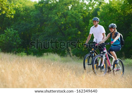 Young Happy Couple Riding Mountain Bikes Outdoor. Healthy Lifestile Concept - stock photo