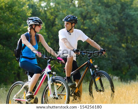Young Happy Couple Riding Mountain Bikes Outdoor. Healthy Lifestyle Concept - stock photo