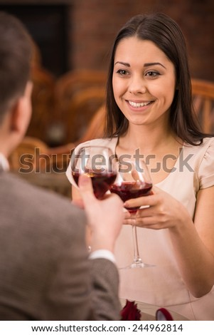 Young happy couple romantic date drink glass of red wine at restaurant. - stock photo
