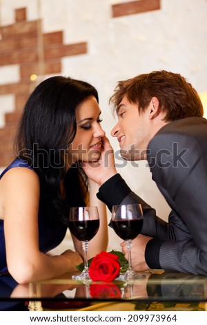 Young happy couple romantic kissing date with glass of red wine at restaurant, celebrating valentine day kiss - stock photo