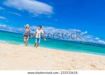 young happy couple running by sand beach on tropical sea background