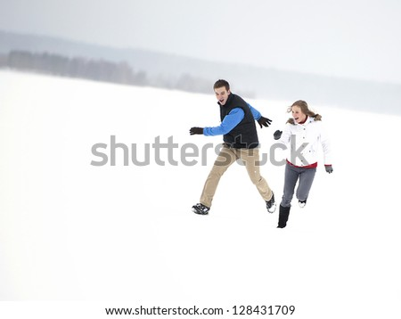 Young happy couple running through a snowy field