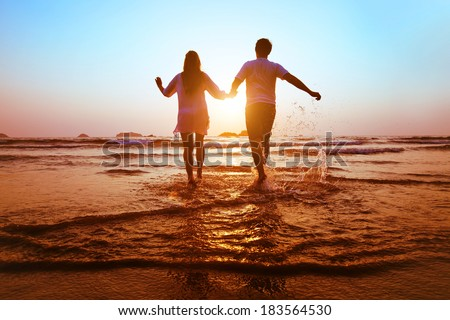 young happy couple running to the sea at sunset beach - stock photo