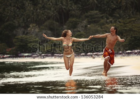 Young happy couple running together along a tropical beach - stock photo