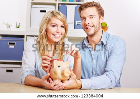 Young happy couple saving Euro money with a piggy bank - stock photo