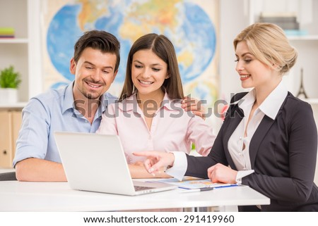 Young happy couple sitting at tourist agency and talking with travel agent. - stock photo