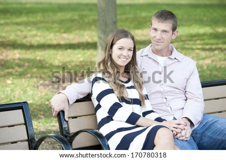 Young happy couple sitting on a bench at the park on a sunny day.