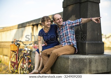 Young happy couple sitting on a old summer promenade.