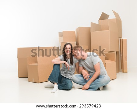 young happy couple sitting on floor in new apartment, exhausted after moving boxes