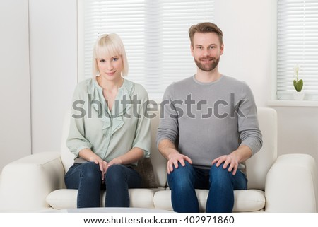 Young Happy Couple Sitting On Sofa In Living Room