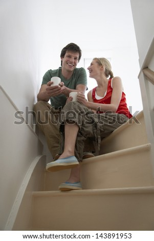 Young happy couple sitting on stairs with coffee cups