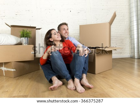 young happy couple sitting on the floor with unpacked cardboard boxes celebrating moving in a new house or apartment flat in real estate mortgage and independent lifestyle concept