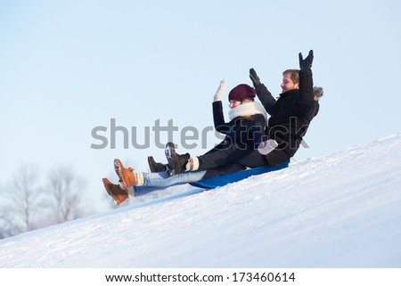 Young happy couple sledging - stock photo