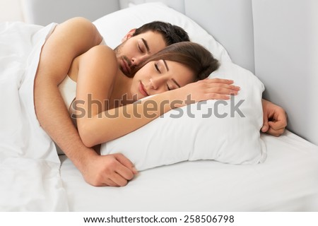 Young happy couple sleeping in bed - stock photo
