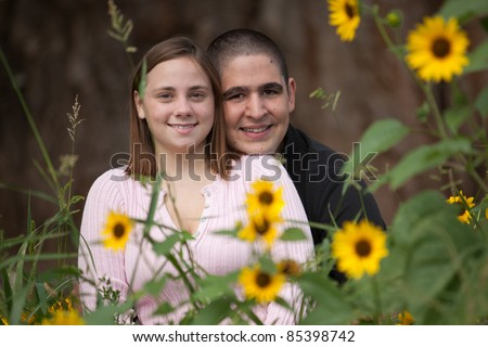 Young happy couple smiling at camera. He is resting his chin on her shoulder in a show of affection
