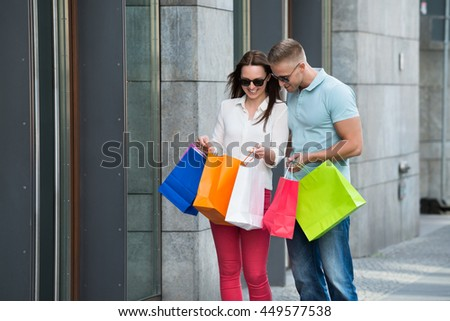 Young Happy Couple Standing On Footpath Holding Multi-colored Shopping Bags - stock photo