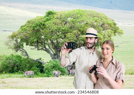 Young, happy couple taking a photo on the safari, Tanzania and Kenya.Acacia tree and animals in the background.Copy space - stock photo