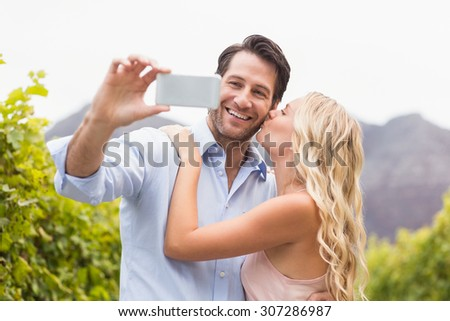 Young happy couple taking a selfie in the grape fields