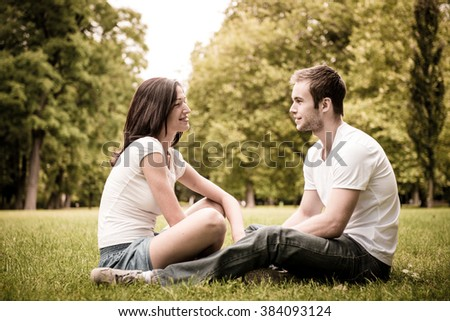 Young happy couple talking together outdoor - sitting on grass - stock photo