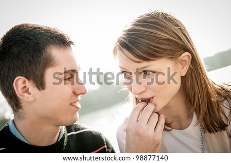 Young happy couple together outdoor - man gives chocolate to woman - stock photo