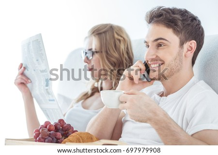 young happy couple using smartphone and reading newspaper during breakfast in bed