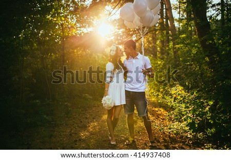 Young happy couple walking in the park. Man holing white baloons balloons. Woman hold white flowers boquet