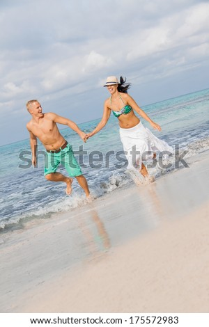 young happy couple walking on beach sunset holiday vacation