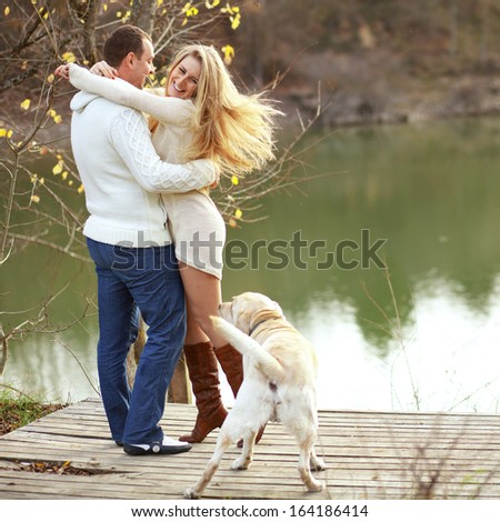 Young happy couple walking with dog near the lake in autumn - stock photo