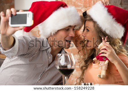 Young happy couple wearing Santa hats looking at one another in restaurant, kissing and taking photos of themselves on mobile phone camera while celebrating Christmas - stock photo