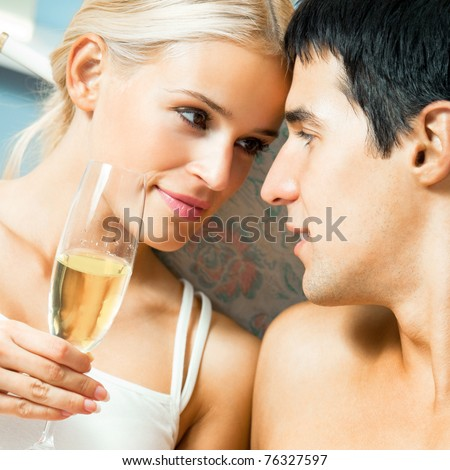 Young happy couple with champagne at bedroom - stock photo