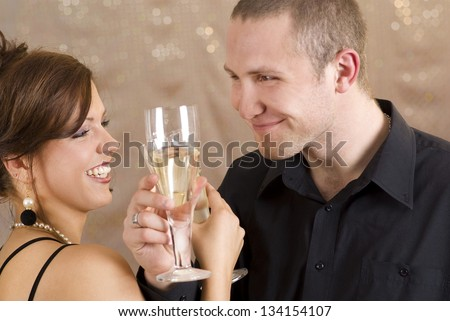 Young happy couple with champagne glasses at celebration.