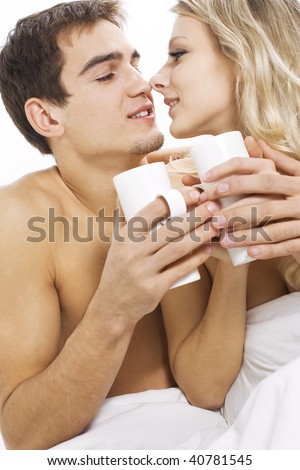 Young happy couple with coffee on the bed in bedroom