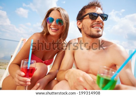 Young happy couple with drinks relaxing on the beach - stock photo