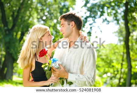 Young happy couple with gift and rose, outdoors. Love, flirt, romantic, relations, celebration theme concept.