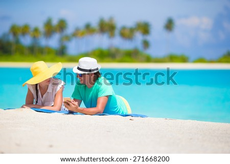 Young happy couple with mobile phone on beach - stock photo