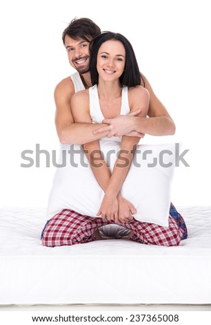 Young happy couple with pillow, isolated on white background. Looking at the camera and smiling.