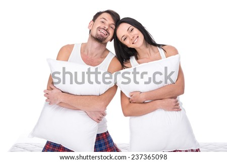 Young happy couple with pillow, isolated on white background. Looking at the camera and smiling. - stock photo