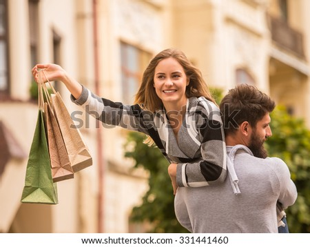 Young happy couple with shopping bags while walking in the city